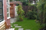 terras met houthok, pergola, gazon, bloemen en speelhuis.