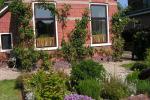 Dorpstuin met verhoogde plantbakken en appelbomen