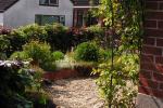 Dorpsvoortuin met grind en verhoogde bloemenbak
